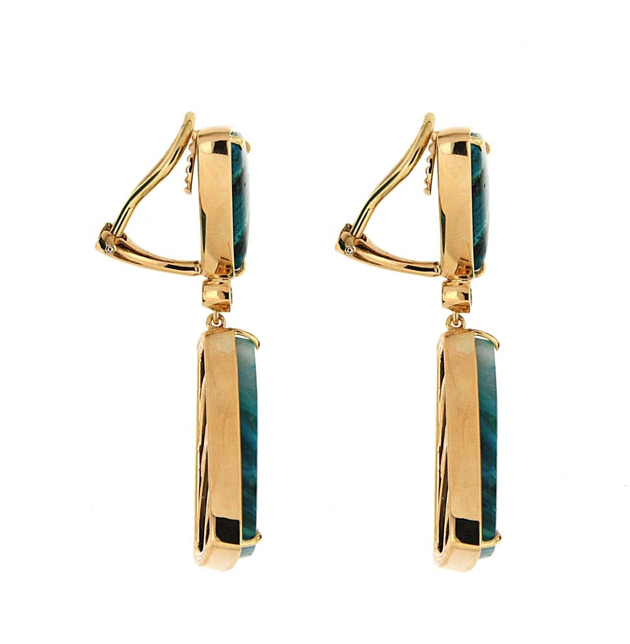 This unique pair of earrings features special cut Chrysocolla Malachite and round brilliant diamonds. The earrings are finished in 18kt Yellow Gold with clip backs.