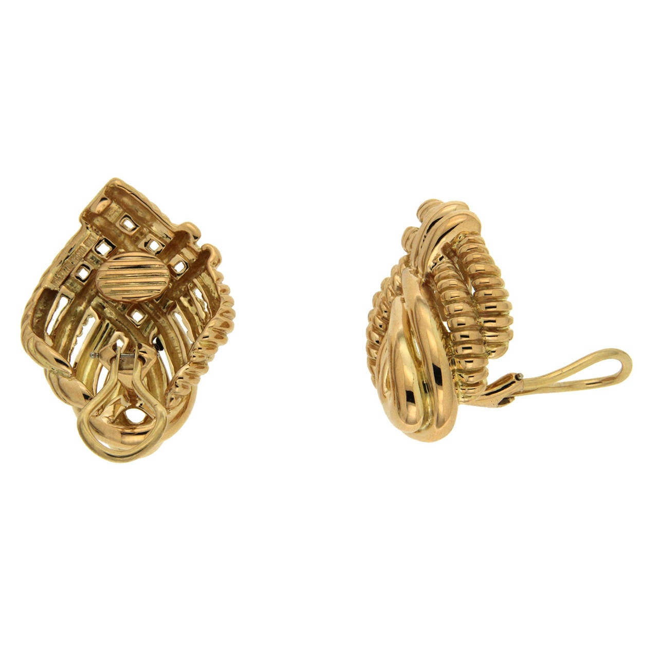 Four lines of gold curve, overlap and twist to create these stunning earrings. Its smooth polish and rope-like texture offer multiple ways to enjoy light playing off their surfaces. The earrings get their warm hues from 18k yellow gold. Clip-backs