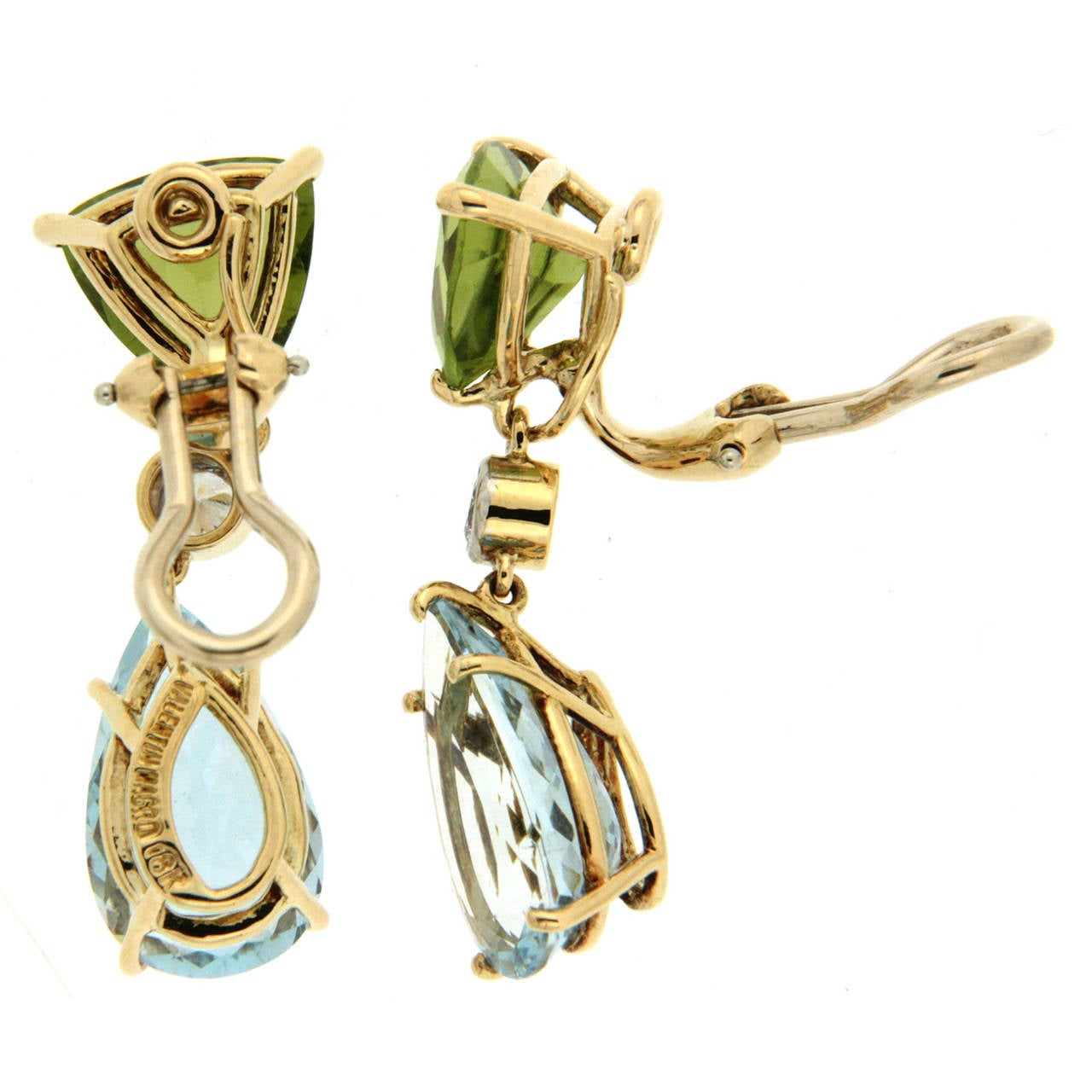 These stylish earrings are made in 18kt yellow gold, they feature trillion peridots, pear shape aquamarine drops and bezel set round brilliant diamonds (0.26ctw), they are finished with clip-backs.