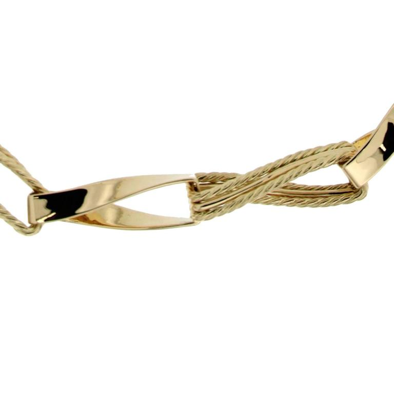 The ribbon necklace is made in 18kt yellow gold. It is 19 inches long and is finished with a unique ring and toggle clasp.
