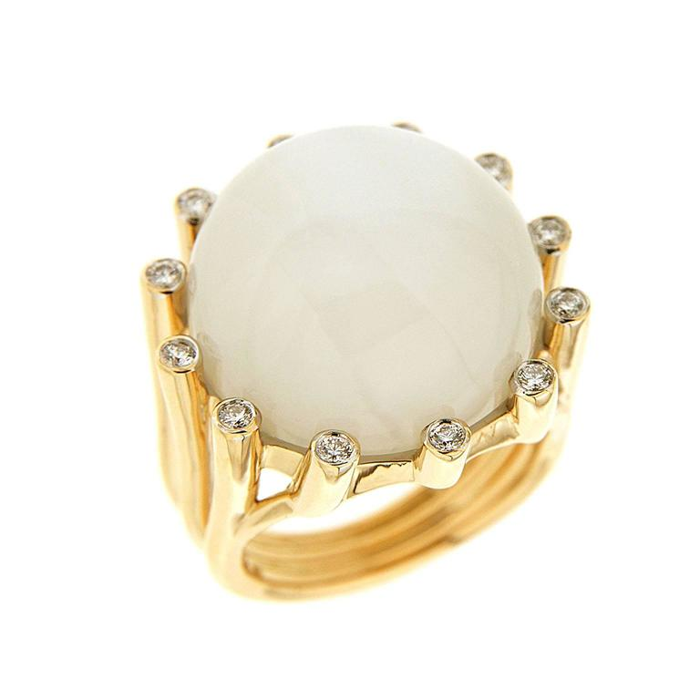 The ring is made in 18kt yellow gold. It features a round moonstone in the center and round brilliant diamonds set in the prongs.