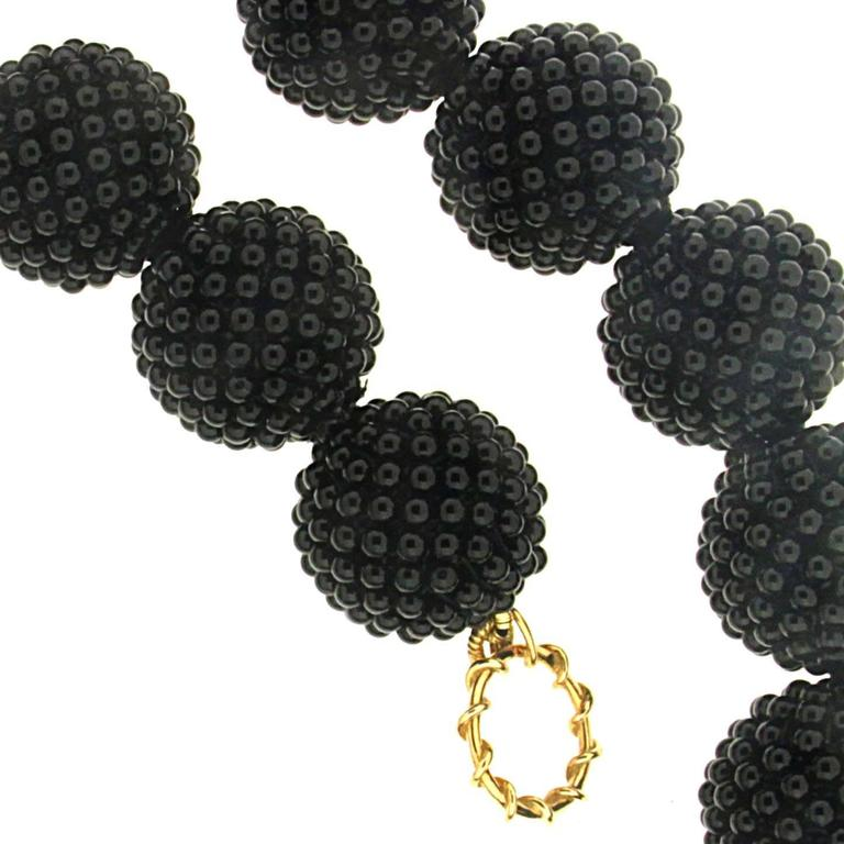 This unique necklace features a strand of 25 Onyx Woven Balls (18mm), it is complete with an 18kt yellow gold ring and toggle clasp.