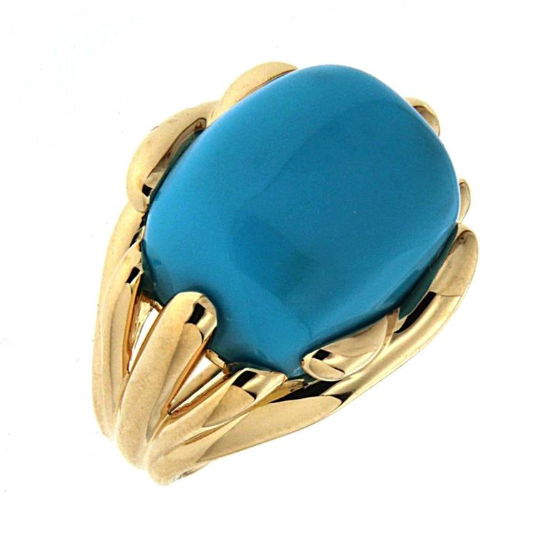 This beautiful ring features a Cushion Cabochon Sleeping Beauty Turquoise 15.52ct  with fluted criss cross designs. The ring is completed in 18kt Yellow Gold.