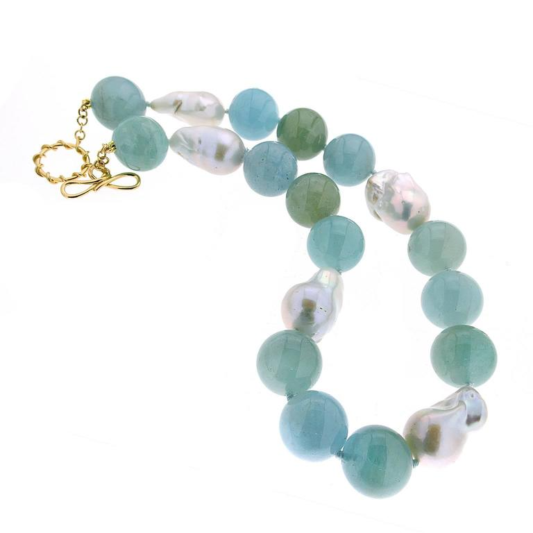 This unique necklace features 20mm aquamarine ball (14) in blue / greenish blue and freshwater pearls with 18kt yellow gold ring and toggle.