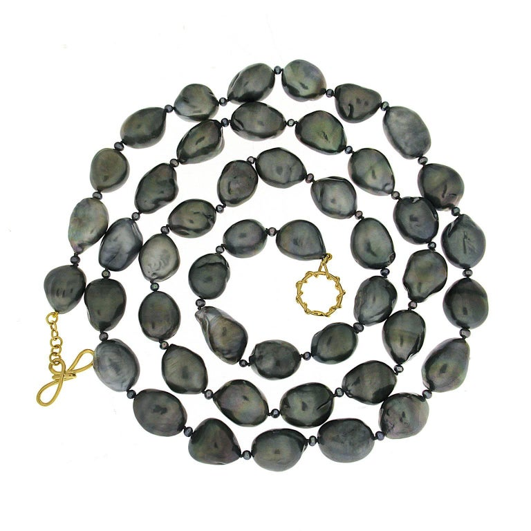 This lovely necklace features 47 Tahitian Keshi Pearls ranging from 18.5x13.5mm to 14.2x13.8mm with small pearls of 2.5mm in between. The necklace is finished with toggle and knot clasp in 18kt yellow gold.