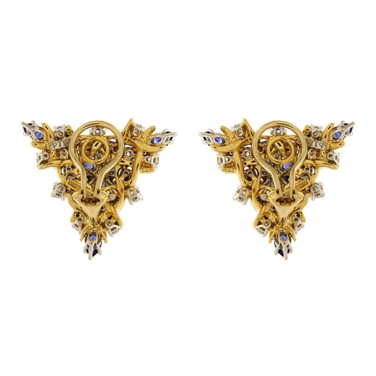 Inspired by nature, this pair of triangular Vine Earrings with pear shape blue sapphires and round brilliant diamonds and 18K yellow gold wire vines. The earrings are completed with clip backs. Diamonds total weight 2.91ct  DEF VVS