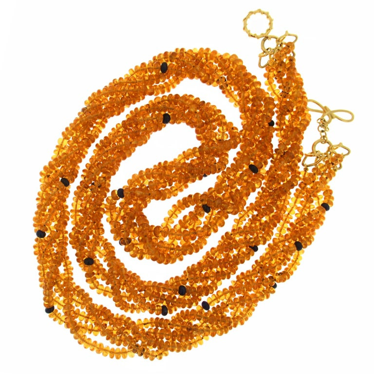 This unique necklace features five strands of mandarin garnet and sapphire rondelles with signature knot ring and toggle in 18kt yellow gold.