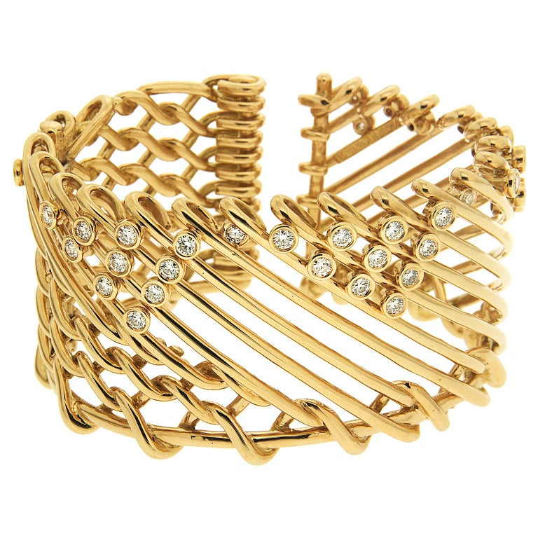 Netting inspired this cuff bracelet created by Valentin Magro. Some of its 18k yellow gold interlocks with one another, forming links. The rest of the bracelet showcases diagonal gold strips. Bezel set round brilliant cut diamonds add brightness and