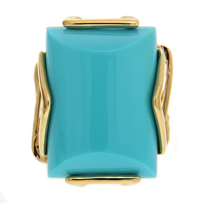 This ring has a surprise from every angle. Its showcase jewel is special cut turquoise with a cylindrical shape and defined edges. The gem rests between 18k yellow gold triangles and trapezoids. Underneath is a double shank with a woven motif