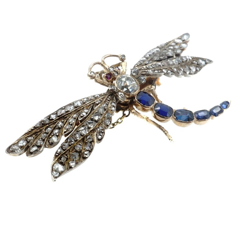 The dragonfly is crafted in 14 karat rose gold and silver featuring an old european cut diamond on the body and rose cut diamonds on moveable wings mounted on springs.  The tail is enhanced with 6 sapphires and the eyes are set with rubies.  Weighs
