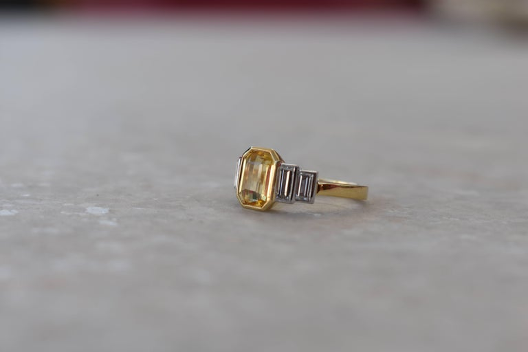 A sophisticated Sri Lankan yellow emerald cut sapphire and baguette diamond ring. 18 karat yellow and white gold surround the yellow, no heat sapphire, and tapered baguette diamonds. Perfect as a dress ring or engagement ring. Comfortable to wear as