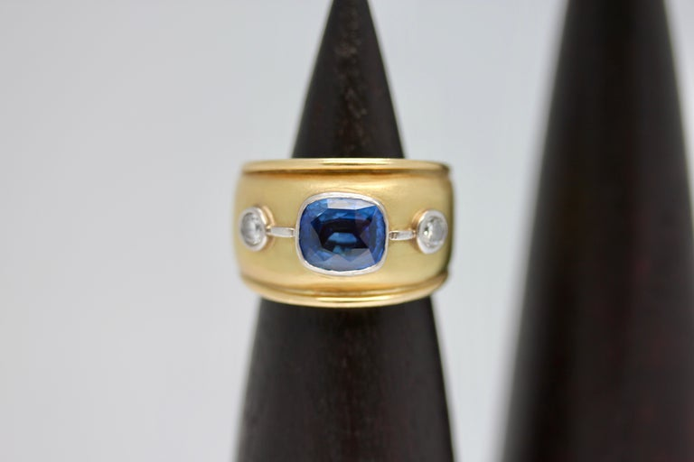 Stunning Sri Lankan blue sapphire and white diamond 18 karat yellow gold cocktail ring. A beautiful and modern design featuring a blue sapphire and two round diamonds set into a comfortable and elegant design.   This item is made bespoke, lead time