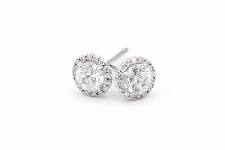 1.00 Carat Diamond Halo Stud earrings in 14K White Gold Center Diamonds are .85 carats total , F color, SI2 clarity Surrounded by 32 diamonds weighing an additional .15 cts.  Total diamonds weight is 1.00 cts  Has the look of 1 carat each diamonds
