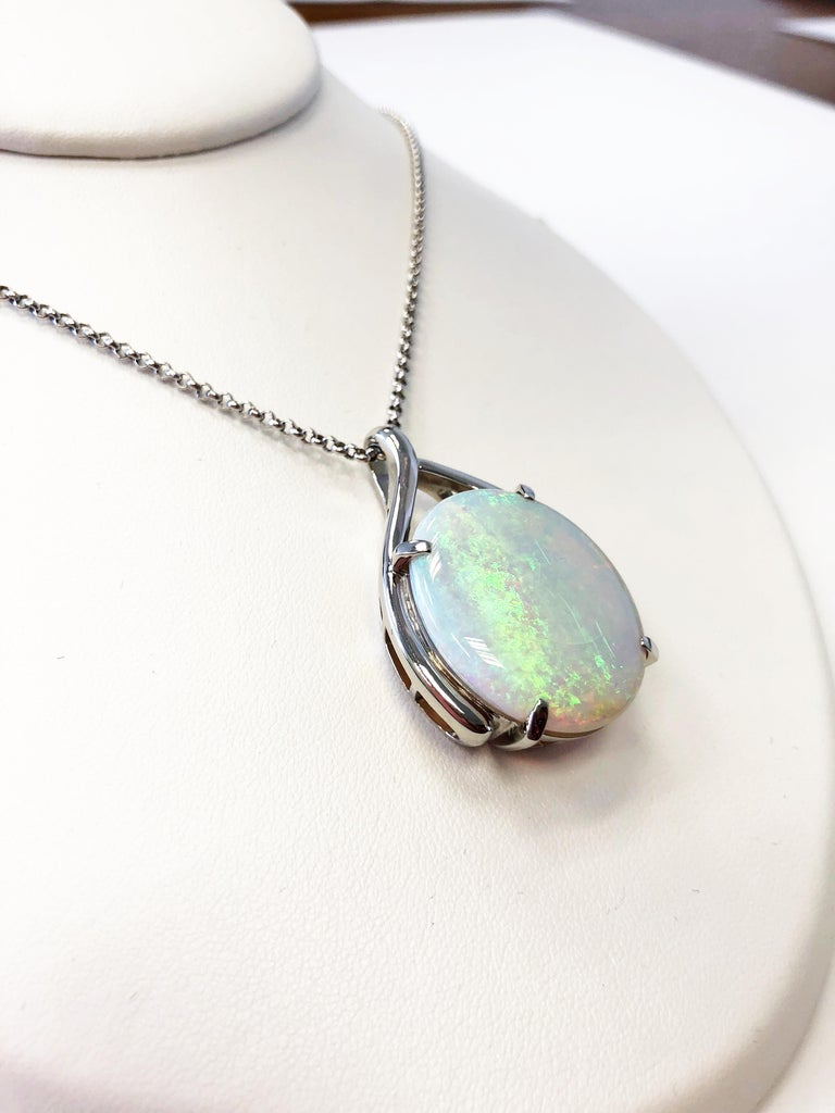 Beautiful 24.13 carat opal oval that has hues of green and orange.  Set in platinum with a 19 inch chain.  This necklace is ideal for someone who appreciates the fire in opals.  A lovely piece to add to any jewelry collection and perfect to wear for