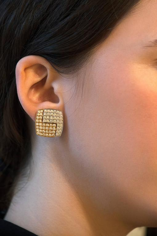 A pair of geometric, 18 karat gold clip-on earrings with approximately 3.9 carats of brilliant cut diamonds made by the admired Swiss master goldsmith, Paul Binder. These earrings measure 0.75