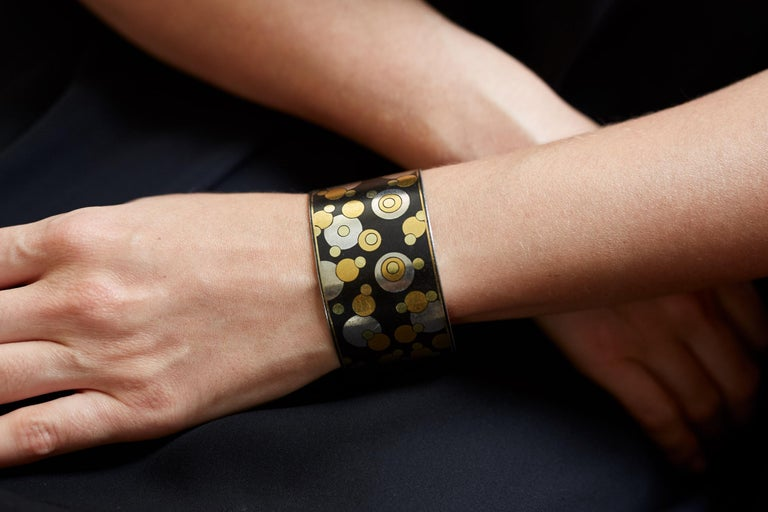 A black iron lacquer and inlaid yellow gold and sterling silver bubble cuff, by Angela Cummings for Tiffany & Co., c. 1980  The cuff measures 5.5