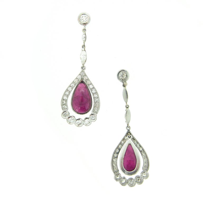 This pair of pendant earrings is very elegant. They are made in 18kt white gold. They feature two cabochon pear shaped tourmaline surrounded by diamonds. There are 46 round cut diamonds weighing an approximate total carat weight of 1ct and there are