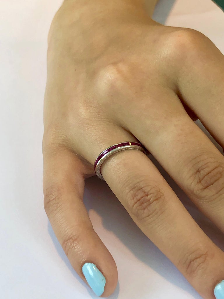 18 karat engraved white gold eternity baguette ruby band Baguette shape ruby weighing 1.65 carats  Engraving on sides of the band Channel set wedding or anniversary ring.  New Ring Our team of graduate gemologists carefully hand-select every