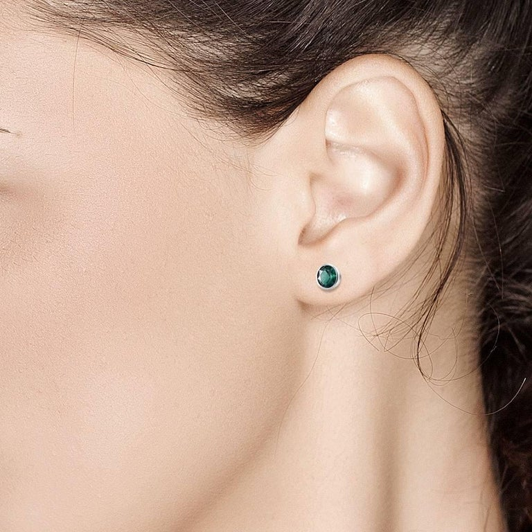 Featuring 14k  white gold bezel-set 5.25mm Colombian emerald stud earrings  Emerald weight 0.90 carats Width of the earrings is 6.5 mm New Earrings Handmade in USA Our team of graduate gemologists carefully hand-select every diamond and gemstone Our