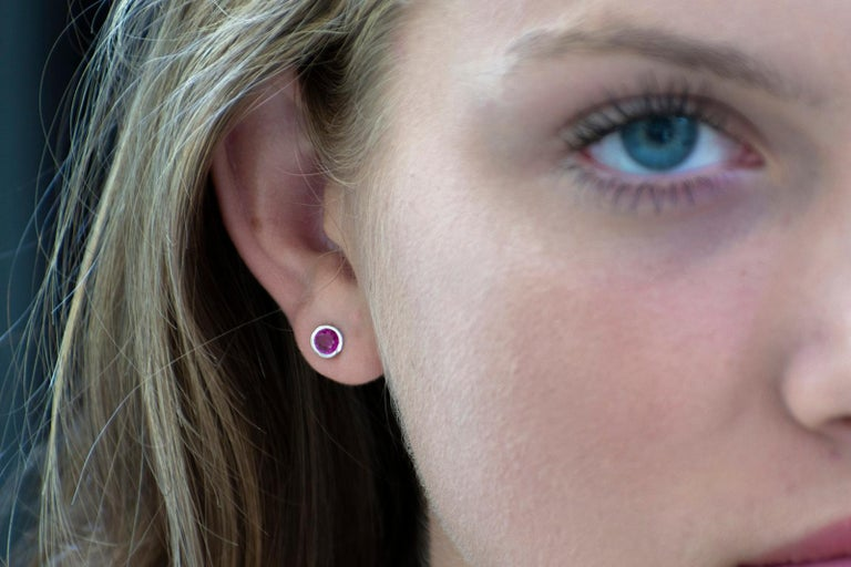 Round Cut White Gold Ruby Weighing 1.00 Carat Bezel Set Stud Earrings For Sale