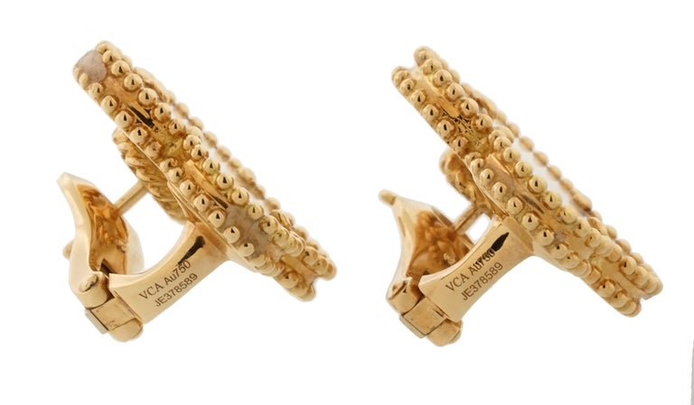 previously-owned Van Cleef Magic Alhambra Collection earrings. The pair of earrings are 20mm wide, made of 18K yellow gold, and weighs 7.70 DWT (approx. 11.97 grams). It also has two clover white mother of pearls.  Designer Van