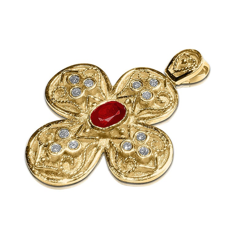 S.Georgios Byzantine Style Cross is handmade from solid 18 Karat Yellow Gold and features a Ruby oval shape total weight of 0,70 Carat and Diamonds total weight of 0,24 Carat. This art piece is made as an inspiration from the Byzantine Museum in