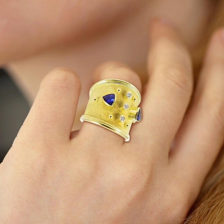 S.Georgios designer 18 Karat Solid Yellow Gold Ring all handmade with Byzantine workmanship and unique velvet look in the background. The ring has Granulation work and is decorated microscopically and features two natural trillions cut Tanzanites