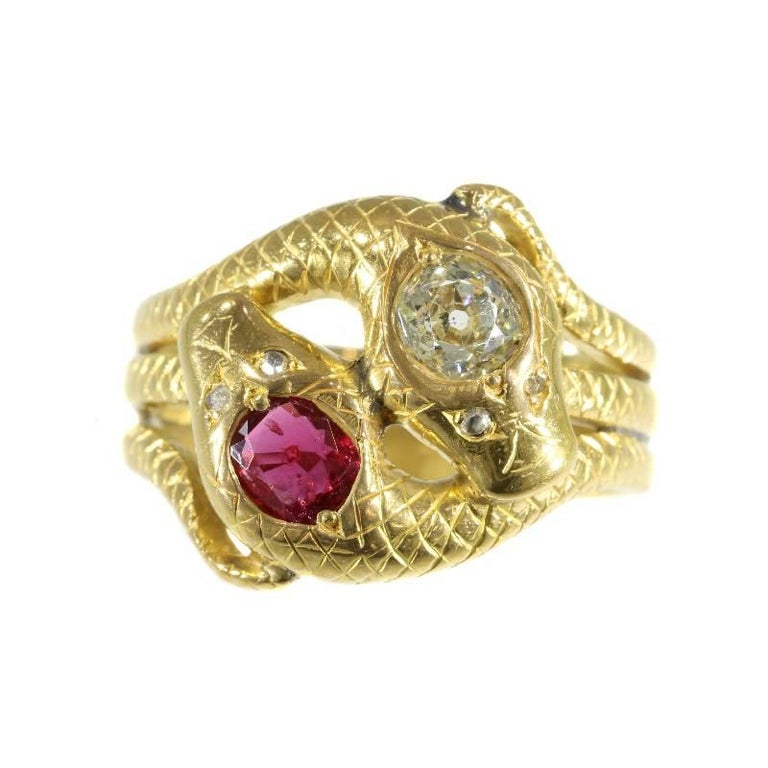 A fine Victorian double snakes ring in 18 karat yellow gold set with .51 carat ruby and .68 carat old European cut diamond (colour and clarity: fancy light yellow, i). Band width on top of ring 1,85 cm (0,73 inch). Ring size US 10, can be sized.