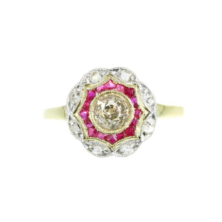 An Art Deco ring in 18 karat yellow and white gold set with a center old European cut diamond weighing .53 carat (colour and clarity: M, i), eight rose cut diamonds and 16 lab produced rubies. Diameter top of ring 1,20 cm (0,47 inch). Ring size 7½,