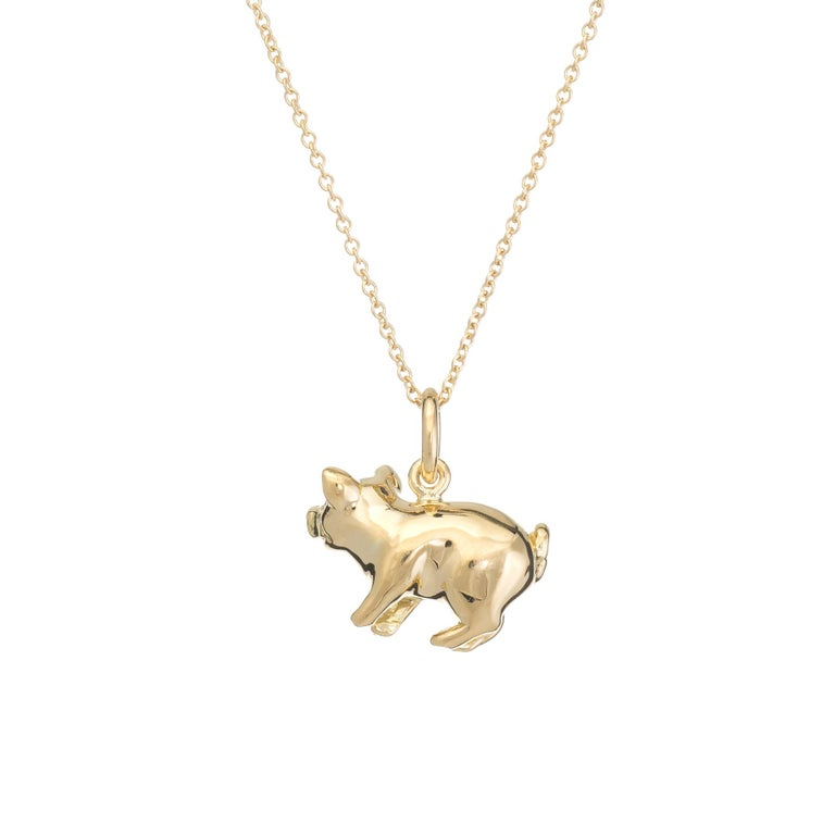 Finely detailed Tiffany & Co pig charm, crafted in 18 karat yellow gold.    Two diamonds are embedded into the eyes and total an estimated 0.02 carats (estimated at F-G color and VVS2 clarity).   Tiffany & Co necklace included (measures 16