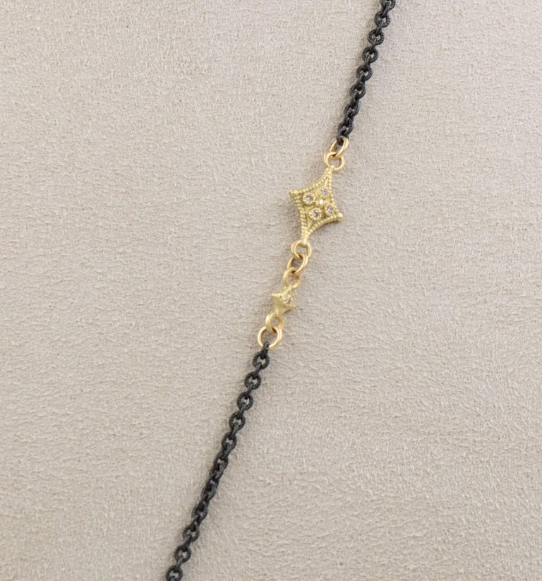 This Armenta lariat necklace from the Old World collection features a 22 inch blackened sterling silver chain with 18 karat yellow gold accents. It also has 12mm bead pendant with pave-set diamonds.   Internal Measurements:  Total Carat Weight: