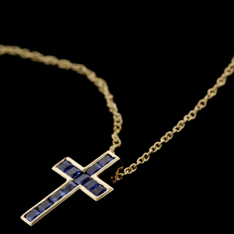 Tiffany & Co. 18K Yellow Gold Sapphire Cross. The cross is channel set with 11 square cut sapphires, approx. total wt. .65cts., length 5/8