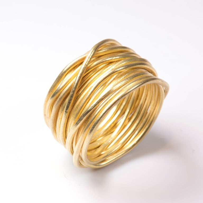 18k yellow gold wire ring. 1mm wire has been lightly textured using traditional forging techniques. One continuous length is wrapped and shaped to form a 9mm wide contemporary and stylish ring. The 'Spaghetti Ring' is a classic design from Disa