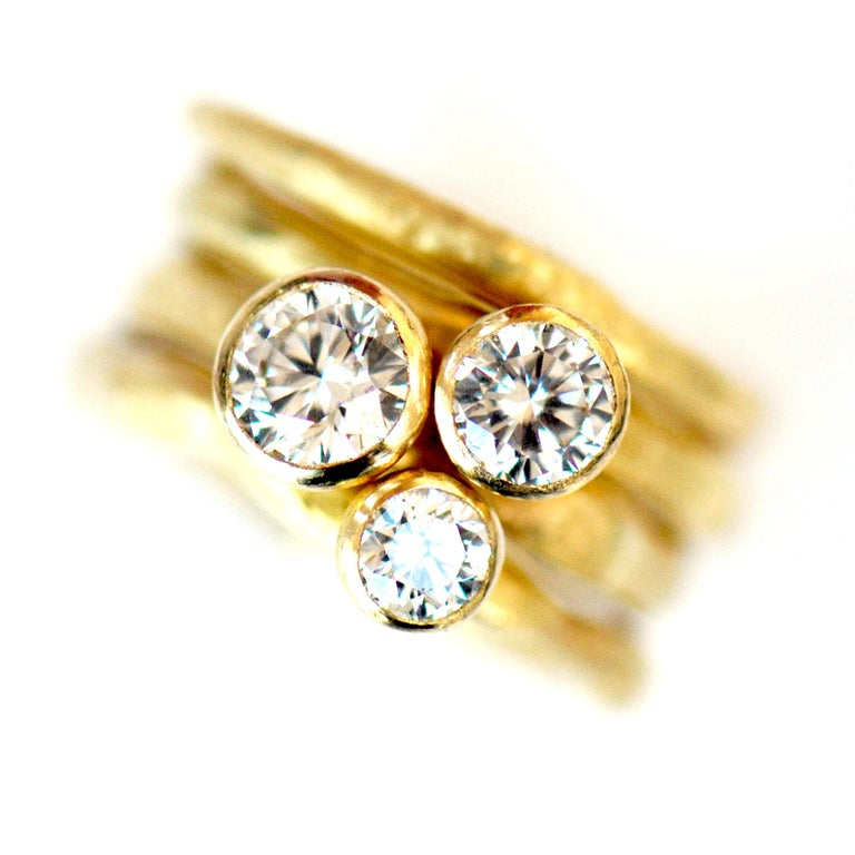 Composed of four rings, this ring stack is made from 18k yellow gold and three certified white diamonds descending in size starting at 1 carat, 0.5 carat, and finally the 0.3 carat. Finished off with a textured band, this would make a beautiful