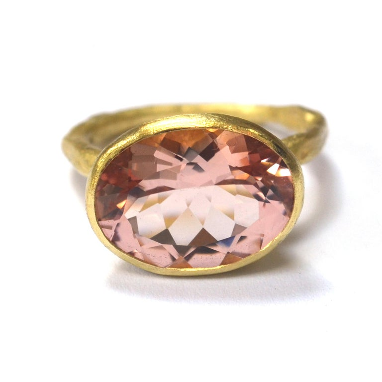 18k yellow gold reticulated melted texture ring with 12mm x 16mm oval 7ct rose hue Morganite. This stone is a particularly desirable shade, framed by a rubover setting that tapers in towards the ring. The setting is 8mm deep. The band is 2.5mm width