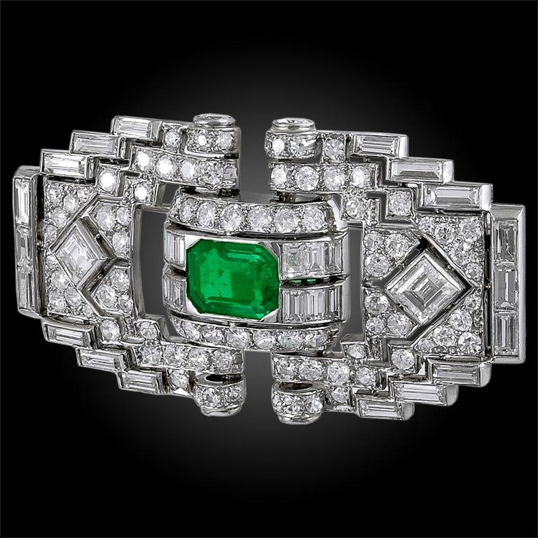 A stunning art deco diamond brooch of geometric openwork design, crafted in the 1920s, centering an outstanding emerald cut emerald of exceptional brilliance at the center of round, baguette and emerald cut diamonds. Signed Mauboussin. Made in France