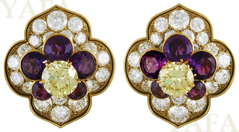 Vintage brooch of quatrefoil design centering upon a cut-cornered square-cut fancy vivid yellow diamond, weighing approximately 3.28 carats, to the four diamond and amethyst flower clusters, each centering upon round brilliant-cut diamonds,