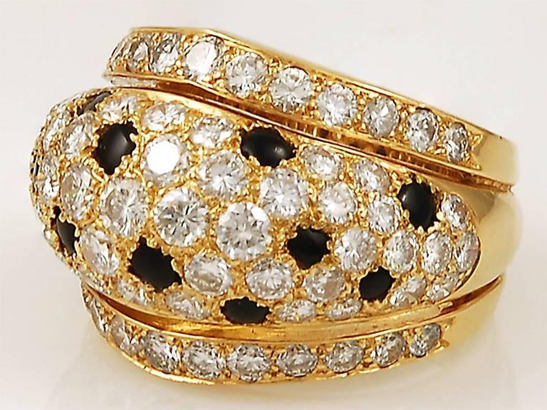 A truly classic Cartier ring, with a domed central section set with brilliant-cut diamonds interspersed with cabochon onyx 'spots' in the iconic cartier 'Panthère' motif, and bordered with two further rows of diamonds. Size 56.