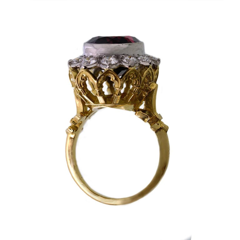 This divine ring is titled The Infinite Rapture ring and is one of a kind. Handmade in 18kt yellow and white gold this glorious ring features a central, deep red garnet approximately 11ct in weight. A halo of 12 diamonds surround the garnet weighing