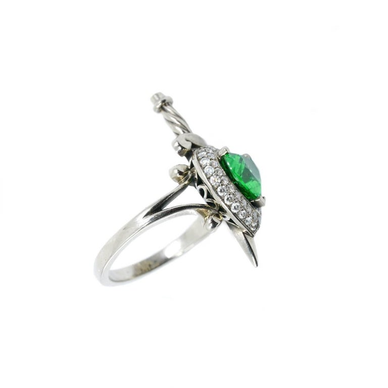 This luxurious Heart and Dagger ring has been handmade from 18kt white gold and features a central, heart cut, tsavorite garnet, approximately 1.50ct in weight and vivid green in colour. A vibrant halo surrounds this astounding stone, made up of 52