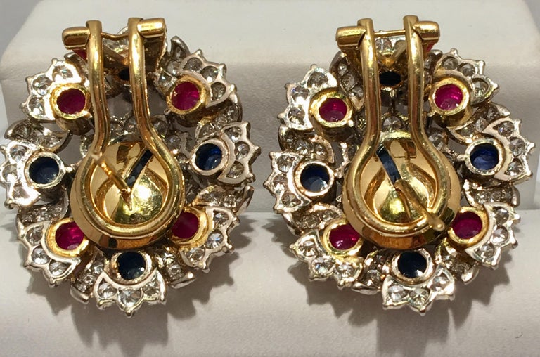 Cabochon oval sapphire, round sapphire, round ruby and diamond earrings feature retractable posts, suitable for both pierced and non-pierced ears.  Posts are hinged and may be folded down to become clip-on earrings with lever backs.  Earrings have