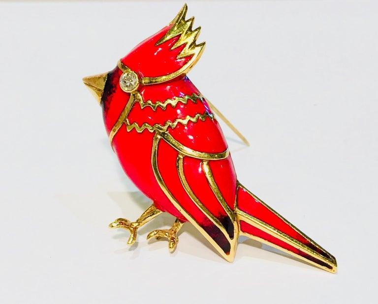 18 karat yellow gold brooch with predominantly red enamel overlay is a stylized Cardinal bird with a bezel set diamond eye .  Diamond measures 3mm in diameter and weighs approximately .11 carats.   Face of brooch pin measures 37.27 mm x 52.64 mm x