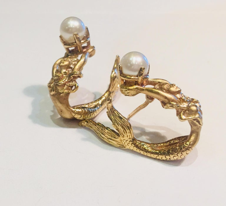 14 karat yellow gold earrings are a pair of beautifully detailed, 3 dimensional mermaids holding one prong set lustrous white pearl, with graceful tails that wrap around the ears.  Pearls measure 5.65 mm each.   Earrings measure 26.17 mm x 21 mm x