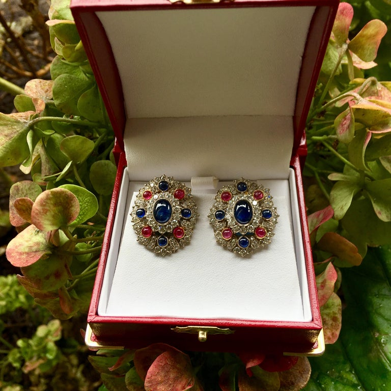 Very elegant, red round cabochon ruby, oval blue sapphire, round blue sapphire, and white diamond earrings feature retractable posts, suitable for both pierced and non-pierced ears.  Posts are hinged and may be folded down to become clip-on earrings