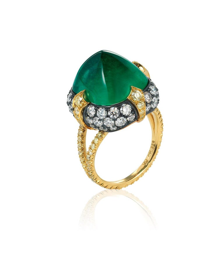 A unique 18kt yellow gold and oxidized silver ring centered upon a superb 11.28 carat sugarloaf Colombian emerald, certified by AGL and C.Dunaigre, set atop a pillow of pavé colorless diamonds and held in place by four 18kt yellow gold