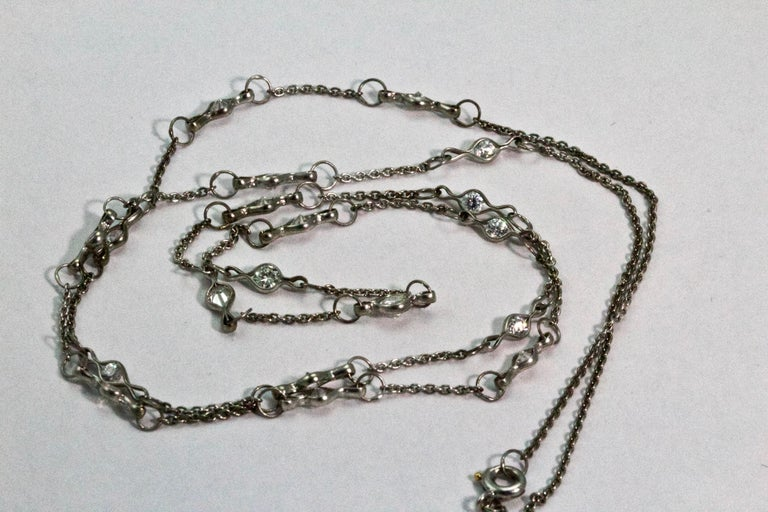 Fashioned circa 1920s this Art Deco long chain is comprised of platinum cable style links to give a chain of approximately 23 inches long. Beautifully embellished with 19 Old European cut diamonds in stylised links. The largest central diamond