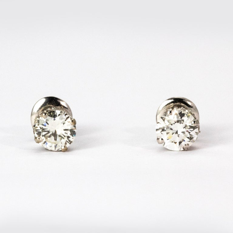 Each of these wonderful Art Deco stud earrings boats a bright old European cut central diamond certified weight 97 points each, colour H and clarity VS2. The ornate bezels are elegantly designed and diamond encrusted, set in platinum.  Certification