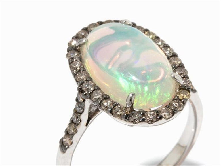 - 750 white gold - Punched with the fineness - 1 Crystal Opal cabochon, approx. 3.15 ct (approx. 15 x 8.7 mm) - 34 brilliant-cut diamonds, total approx. 0.5 ct, in brown colour - Ring size: 53; US 6,4 - Weight: approx. 4.2 g  Beschreibung ·750