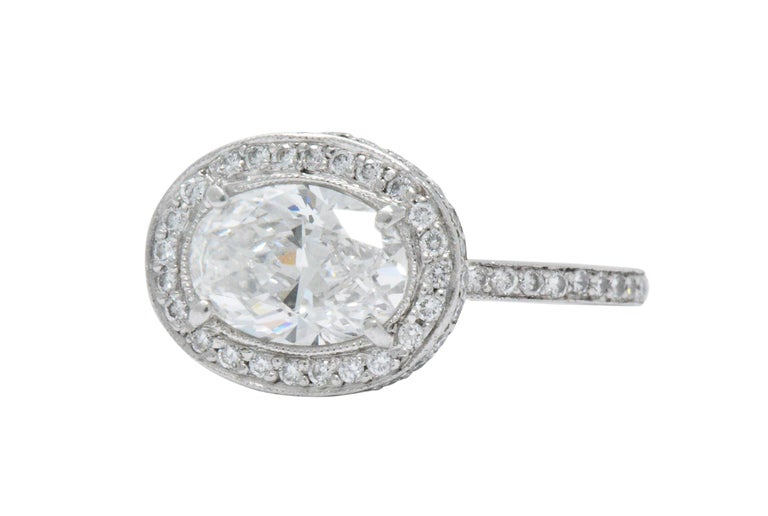 Centering an oval cut diamond weighing 1.41 carats, E color and VS2 clarity  Diamond accents on top, amidst the sides, under the head and along the shank, approximately 0.55 carats total, G/H color and VS to SI clarity  Top of the ring measures 10.4