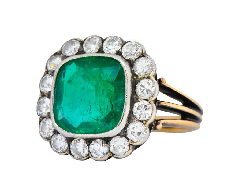 Centering a square cushion cut emerald weighing approximately 3.25 carats, bright vivid green  With an old European cut diamond surround weighing approximately 1.60 carats, GHI color and VS to SI clarity  With a tri-split and grooved shank  Tested